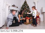 Семья- папа, мама и мальчик четырех лет на Новый год и рождество у елки с подарками и часами (2011 год). Редакционное фото, фотограф Вероника Горбова / Фотобанк Лори