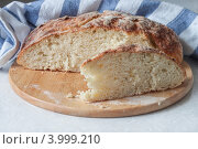Буханка хлеба и отрезанный кусок. Стоковое фото, фотограф Виктория Козикова / Фотобанк Лори