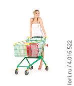 Купить «Симпатичная молодая женщина после шоппинга с покупками в покупательской тележке на белом фоне», фото № 4016522, снято 26 сентября 2009 г. (c) Syda Productions / Фотобанк Лори