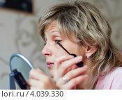 Купить «Ухоженная женщина средних лет  красит ресницы тушью», эксклюзивное фото № 4039330, снято 20 сентября 2012 г. (c) Игорь Низов / Фотобанк Лори