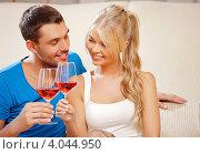 Купить «Счастливая молодая пара пьет дома вино из бокалов», фото № 4044950, снято 4 августа 2012 г. (c) Syda Productions / Фотобанк Лори