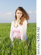 Купить «Портрет кудрявой девушки с травинкой во рту на фоне летнего пейзажа», фото № 4054142, снято 7 мая 2011 г. (c) Сергей Сухоруков / Фотобанк Лори