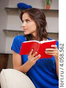 Привлекательная юная девушка читает книгу дома, сидя на диване. Стоковое фото, фотограф Syda Productions / Фотобанк Лори