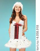Купить «Симпатичная молодая женщина в колпаке Санты-Клауса, короткой юбке и длинными волосами с подарком в руках», фото № 4058918, снято 22 ноября 2011 г. (c) Syda Productions / Фотобанк Лори