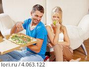Купить «Девушка грызет зеленое яблоко, а молодой человек ест вредную пиццу на фоне дивана дома», фото № 4063122, снято 4 августа 2012 г. (c) Syda Productions / Фотобанк Лори
