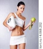 Купить «Девушка в спортивной форме стоит на сером фоне и держит в руках яблоко, сантиметр и напольные весы», фото № 4068202, снято 2 ноября 2012 г. (c) Валуа Виталий / Фотобанк Лори