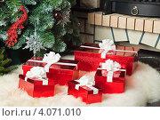 Купить «Красные подарочные коробки лежат на ковре около новогодней елки и камина», фото № 4071010, снято 4 ноября 2012 г. (c) Оксана Гильман / Фотобанк Лори