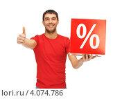 Купить «Привлекательный счастливый молодой человек в красной футболке с пакетом со знаком процентов в руках», фото № 4074786, снято 7 октября 2012 г. (c) Syda Productions / Фотобанк Лори
