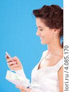 Купить «Счастливая невеста с деньгами и калькулятором в руке на голубом фоне», фото № 4085170, снято 5 сентября 2009 г. (c) Syda Productions / Фотобанк Лори