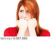 Купить «Несчастная рыжая женщина кусает кулаки на белом фоне», фото № 4087886, снято 10 октября 2009 г. (c) Syda Productions / Фотобанк Лори