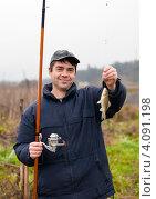 Купить «Счастливый рыбак с пойманной рыбой на крючке и удочкой в руках», эксклюзивное фото № 4091198, снято 5 ноября 2012 г. (c) Игорь Низов / Фотобанк Лори