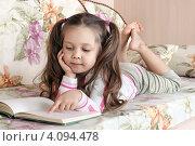 Купить «Маленькая девочка читает книгу, лежа на диване», фото № 4094478, снято 21 августа 2018 г. (c) Игорь Долгов / Фотобанк Лори