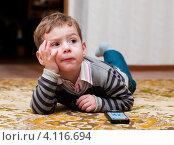 Маленький мальчик лежит на ковре с пультом от телевизора (2012 год). Редакционное фото, фотограф Игорь Низов / Фотобанк Лори