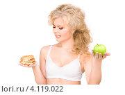 Купить «Привлекательная блондинка выбирает между яблоком и гамбургером», фото № 4119022, снято 21 ноября 2009 г. (c) Syda Productions / Фотобанк Лори