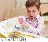 Маленький мальчик рассматривает книгу (2012 год). Редакционное фото, фотограф Игорь Низов / Фотобанк Лори