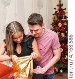 Купить «Счастливая пара. Парень с девушкой открывают мешок с подарками возле новогодней ёлки», эксклюзивное фото № 4168586, снято 5 января 2013 г. (c) Игорь Низов / Фотобанк Лори