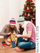 Счастливая пара. Девушка и парень сидя на полу рассматривают подарки в мешке возле новогодней ёлки. Стоковое фото, фотограф Игорь Низов / Фотобанк Лори