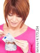 счастливая молодая женщина кладет деньги в кошелек. Стоковое фото, фотограф Syda Productions / Фотобанк Лори