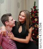 Купить «Счастливая пара. Красивая девушка и парень сидят в обнимку возле новогодней ёлки», эксклюзивное фото № 4176594, снято 5 января 2013 г. (c) Игорь Низов / Фотобанк Лори