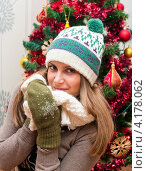 Красивая девушка в зимней шапке дома на фоне новогодней ёлки. Стоковое фото, фотограф Игорь Низов / Фотобанк Лори
