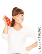 Купить «Привлекательная девушка с челкой держит в руке гроздь красных помидоров», фото № 4196090, снято 27 июня 2010 г. (c) Syda Productions / Фотобанк Лори