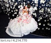 Молодожены целуются в комнате, украшенной висящими стеклянными шариками. Стоковое фото, фотограф Антон Куделин / Фотобанк Лори