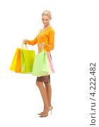 Купить «Счастливая молодая женщина держит в руках покупки в бумажных пакетах на белом фоне», фото № 4222482, снято 18 сентября 2010 г. (c) Syda Productions / Фотобанк Лори