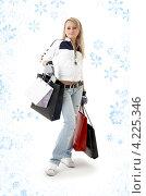 Купить «Юная девушка с пакетами покупок на фоне со снежинками», фото № 4225346, снято 25 февраля 2007 г. (c) Syda Productions / Фотобанк Лори