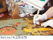 Купить «Реставрация православной иконы, инструмент из агата в руке художника», фото № 4229678, снято 17 января 2013 г. (c) Яков Филимонов / Фотобанк Лори