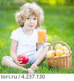 Ребенок со стаканом яблочного сока и корзинкой яблок на траве в летнем парке. Стоковое фото, фотограф yarruta / Фотобанк Лори
