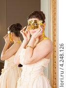 Купить «Молодая брюнетка надевает золотую полумаску, чтобы скрыть свое лицо», фото № 4248126, снято 8 января 2013 г. (c) Сергей Дубров / Фотобанк Лори
