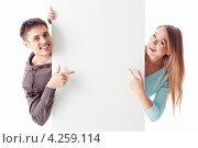 Купить «Счастливая пара выглядывает из за белого баннера на белом фоне», фото № 4259114, снято 13 января 2013 г. (c) Raev Denis / Фотобанк Лори