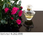 Купить «Флакон духов и букет красных роз на столе», фото № 4262898, снято 27 января 2013 г. (c) Елена Силкова / Фотобанк Лори
