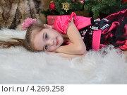 Красивая девочка 9 лет, лежит на белом пушистом ковре на фоне новогодней елки. Стоковое фото, фотограф Вера Зонова / Фотобанк Лори