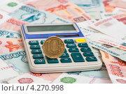 Калькулятор с 10-рублёвой монетой лежит на российских рублях. Стоковое фото, фотограф Игорь Низов / Фотобанк Лори