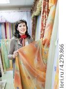 Купить «Девушка выбирает шторы в магазине», фото № 4279866, снято 11 сентября 2012 г. (c) Яков Филимонов / Фотобанк Лори