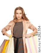 Купить «Очаровательная молодая женщина в бежевом плаще с пакетами покупок в руках», фото № 4282554, снято 10 октября 2010 г. (c) Syda Productions / Фотобанк Лори