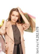 Купить «Очаровательная молодая женщина в бежевом плаще с пакетами покупок в руках», фото № 4282678, снято 10 октября 2010 г. (c) Syda Productions / Фотобанк Лори
