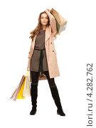 Купить «Очаровательная молодая женщина в бежевом плаще с пакетами покупок в руках», фото № 4282762, снято 10 октября 2010 г. (c) Syda Productions / Фотобанк Лори