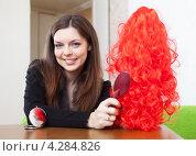 Купить «Девушка расчесывает красный парик», фото № 4284826, снято 21 декабря 2012 г. (c) Яков Филимонов / Фотобанк Лори