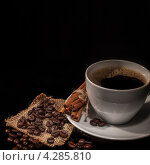 Композиция: чашка кофе,корица, зёрна кофе и мешковина на чёрном фоне. Стоковое фото, фотограф Максим Савин / Фотобанк Лори