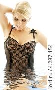 Купить «Очаровательная блондинка в черном белье стоит по пояс в воде», фото № 4287154, снято 30 сентября 2006 г. (c) Syda Productions / Фотобанк Лори