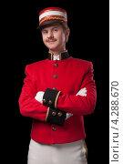 Портрет консьержа на черном фоне. Мужчина в красной форме стоит, скрестив руки на груди. Стоковое фото, фотограф Vycheslav Leskovskiy / Фотобанк Лори