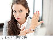 Купить «Молодая девушка в офисе показывает на часы», фото № 4308086, снято 5 августа 2020 г. (c) Syda Productions / Фотобанк Лори