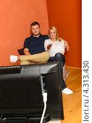 Купить «Влюбленная пара смотрит телевизор», фото № 4313430, снято 25 октября 2012 г. (c) CandyBox Images / Фотобанк Лори