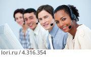Купить «Сотрудники колл-центра смотрят в камеру, сидя на рабочих местах, на переднем плане смуглая брюнетка», фото № 4316354, снято 26 октября 2009 г. (c) Wavebreak Media / Фотобанк Лори