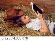 Купить «Девушка в ковбойской шляпе читает книгу на сеновале», фото № 4333078, снято 9 января 2013 г. (c) Дегтярева Виктория / Фотобанк Лори