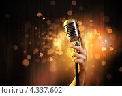 Купить «Микрофон в стиле ретро в руке на фоне с золотым боке», фото № 4337602, снято 21 октября 2018 г. (c) Sergey Nivens / Фотобанк Лори