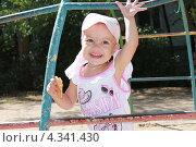 Девочка машет рукой и улыбается на детской площадке. Стоковое фото, фотограф бобух олег / Фотобанк Лори