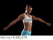 Купить «Красивая загорелая модель в студии выполняет спортивные упражнения на черном фоне», фото № 4342074, снято 4 декабря 2012 г. (c) Sergey Nivens / Фотобанк Лори